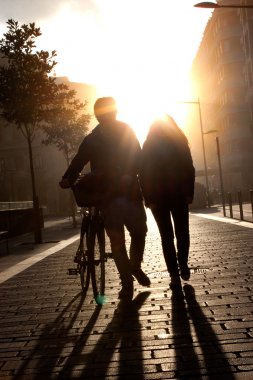 Young couple walking down the street with a bicycle at sunset.