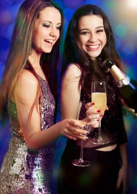 Two beautiful girl friends with champagne at party