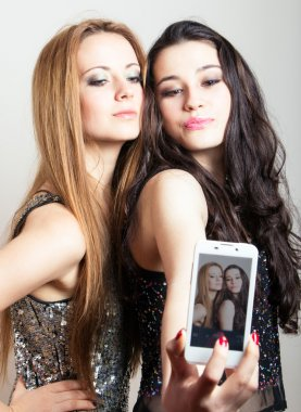 Beautiful girls making a self portrait with mobile