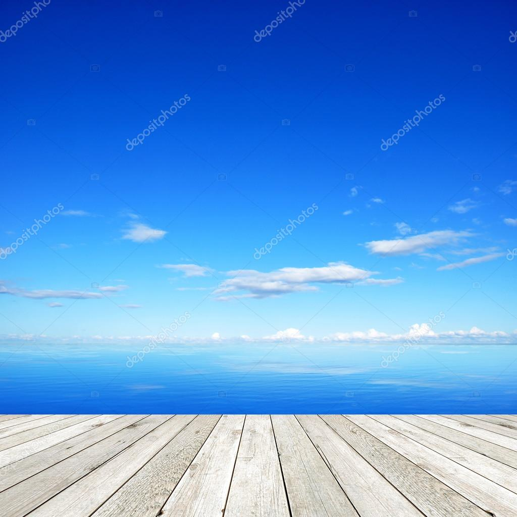 Wooden pier on blue sea and sky background