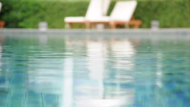 kalužemi vody v bazénu s plážovými lehátky  zelených rostlin pozadí
