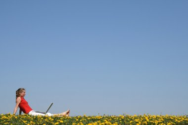 Girl relaxing with laptop in flowering field