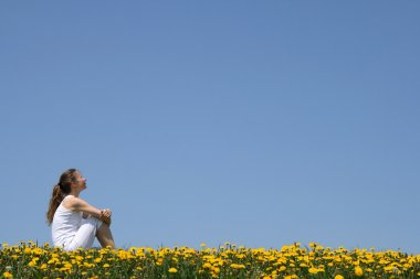 Girl sitting in dandelion field