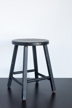 Black shabby stool on wooden surface