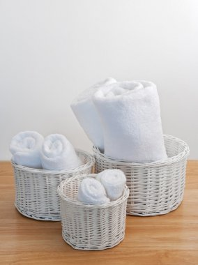 Clean towels in white wicker baskets