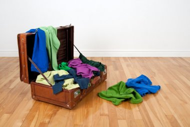Leather suitcase full of colorful clothing