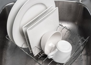 Dishes drying on a rack in the kitchen sink