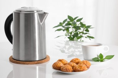 Electric kettle, teacup and cookies
