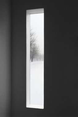 Dark room and winter landscape outside the window