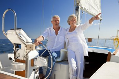 A happy senior couple sitting at the wheel of a sail boat