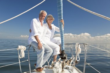 A happy senior couple embracing at the front or bow of a sail boat