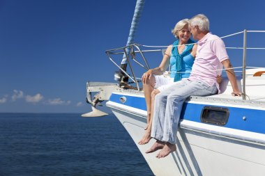 A happy senior couple sitting on the front of a sail boat