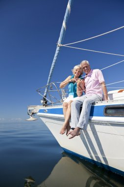 A happy senior couple sitting at the front or bow of a sail boat