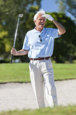 Happy Senior Man Playing Golf In Bunker