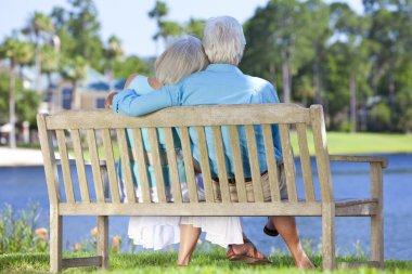 Rear View Senior Couple Sitting On Park Bench Embracing