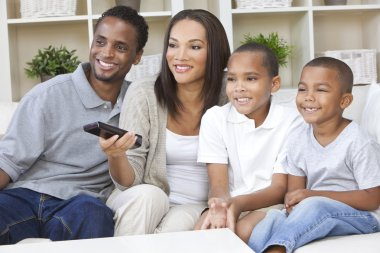 African American Family Watching Television With Remote Control