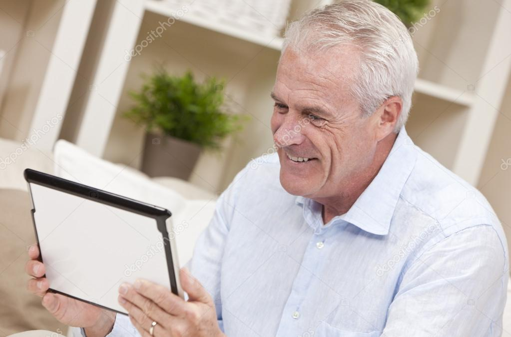 Smiling senior man at home sitting on sofa or settee using her tablet computer.