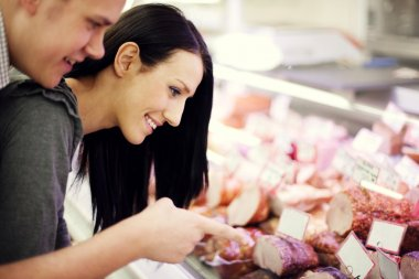 Young couple in butchers shop