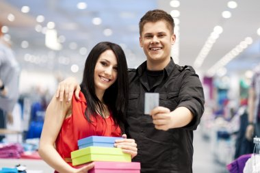 Happy young couple spending money at clothing store