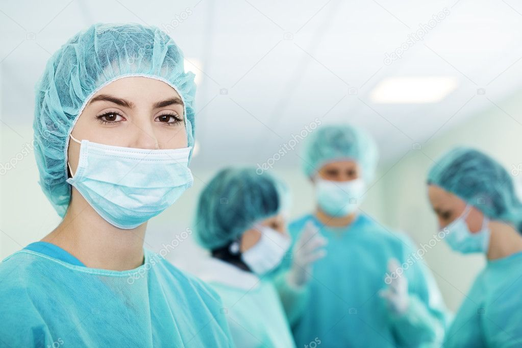 Young female surgeon with medical team in back before surger