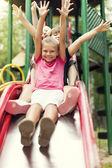 Fotografia scivolo bambini felici sul parco giochi