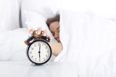 Woman turning off the alarm clock