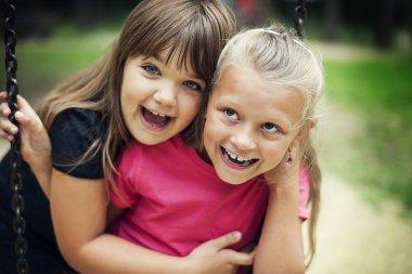 Happy little girls swinging in a park