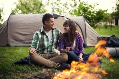 Couple near a campfire toasting marshmallow