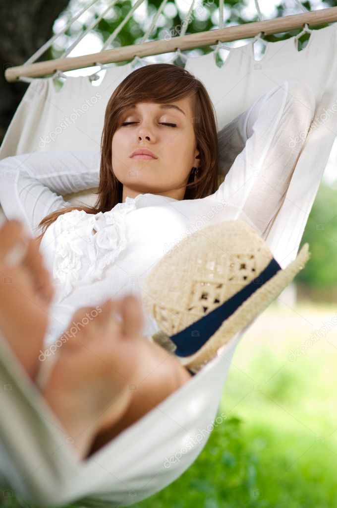 Young woman sleeping on hammock