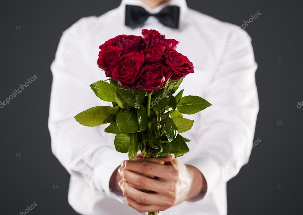 Man giving bouquet of red roses — Stock Photo © gpointstudio #22319919