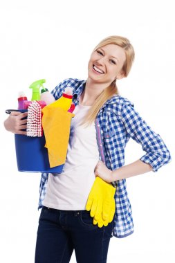 Happy housewife holding cleaning equipment