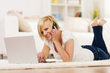 Happy woman using laptop and talking on mobile phone