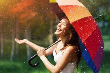 Woman with umbrella checking for rain