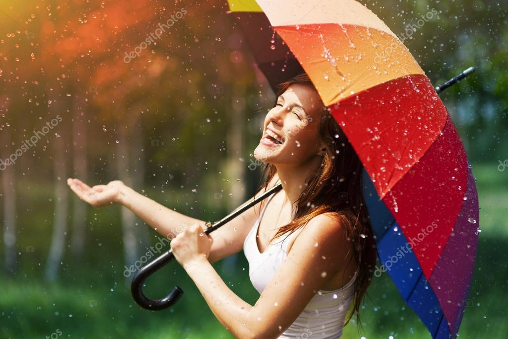 Woman with umbrella checking for rain