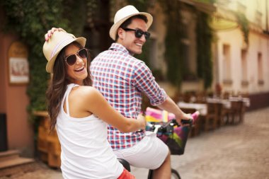 Happy couple riding a bicycle in the city street