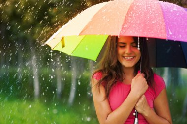 Beautiful woman under rainbow umbrella