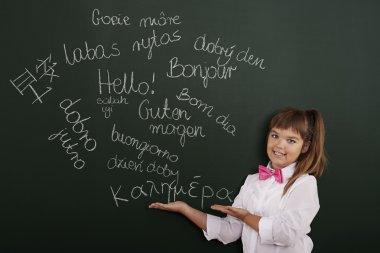 Schoolgirl presenting foreign phrases on blackboard