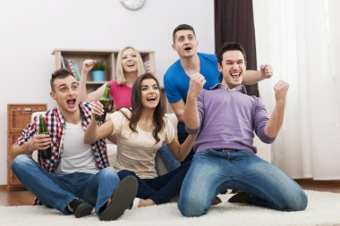 Friends watching TV and cheering soccer