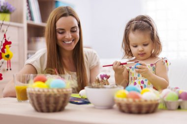 Girl painting easter eggs with her mother