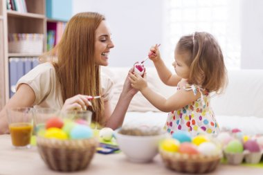Happy mother and baby painting easter egg