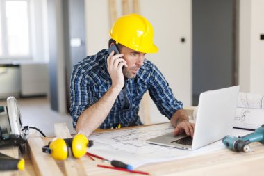 Man talking on mobile phone and using laptop on construction side stock vector
