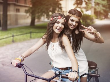 Boho girls on the tandem bicycle