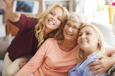 Girl taking selfie with mom and grandma