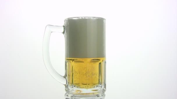 pivní pěna se přelije přes okraj hrnku. bílé pozadí