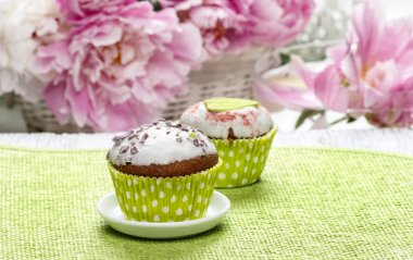 Cupcakes on green napkin. Stunning peony flowers in the backgrou