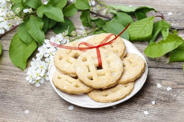 Round biscuits with red bow in spring setting. Wooden table