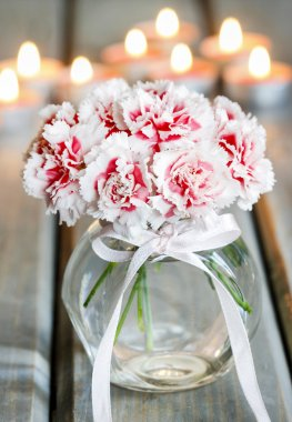 Bouquet of carnation flowers in glass vase on wooden table. Golden candles in the background. Selective focus. stock vector