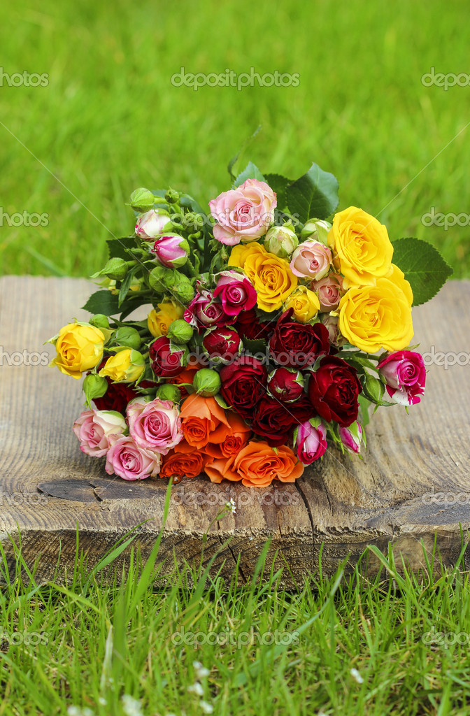 Fabulous bouquet of colorful roses on wooden tray in fresh sprin