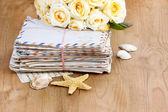 zásobník starých dopisů a kytice pastelově žluté růže na dřevo