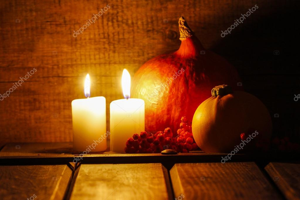 Two small candles burning in old wooden hut. Big orange pumpkin
